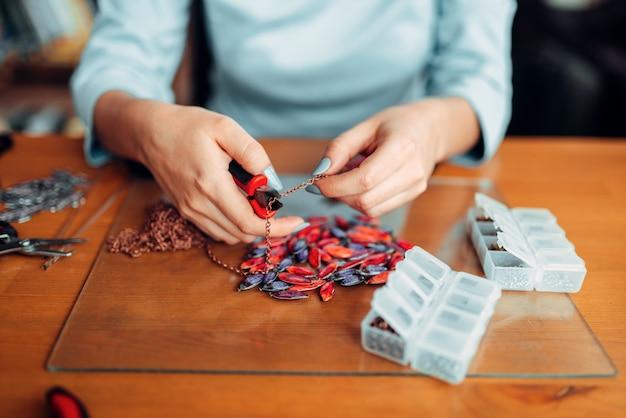 Persona di sesso femminile le mani con le pinze, maestro al lavoro.