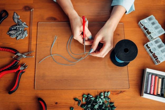 Persona di sesso femminile le mani con le pinze, vista dall'alto. gioielli fatti a mano. ricamo, bigiotteria.
