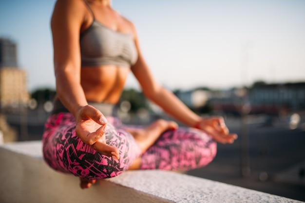 Persona di sesso femminile, relax nella posa yoga, città. esercizio di meditazione yogi all'aperto