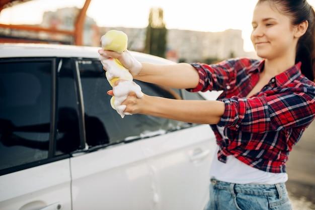 Persona di sesso femminile che pulisce il finestrino del veicolo con schiuma