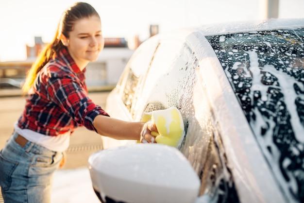 Persona di sesso femminile che pulisce il veicolo con schiuma