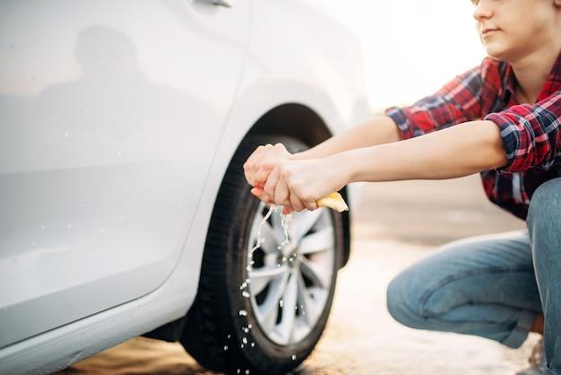 Persona di sesso femminile su autolavaggio self-service, processo di autolavaggio. lavaggio del veicolo all'aperto in una giornata estiva. la donna stringe la spugna dopo la pulizia dell'automobile