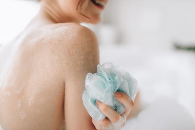 La persona di sesso femminile insapona il corpo con una spugna in bagno. cura del corpo e cura della pelle in bagno