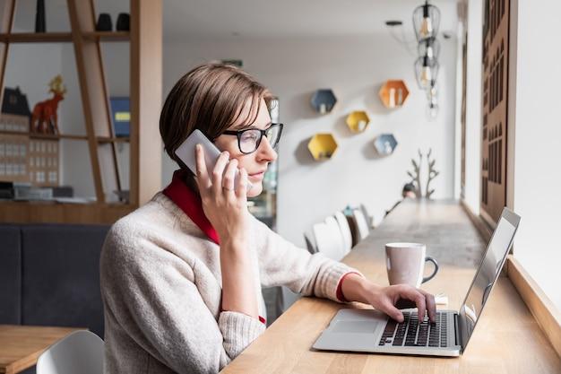 Persona di sesso femminile che parla al telefono e utilizza il computer portatile a pranzo in un caffè. donna d'affari di contenuto che lavora con la tecnologia in un luogo pubblico