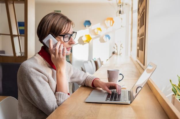 Persona di sesso femminile che parla al telefono e utilizza il computer portatile a pranzo in un caffè illuminato dal sole. donna d'affari di contenuto che lavora con la tecnologia in un luogo pubblico