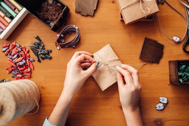 Persona di sesso femminile legare un fiocco su una confezione regalo, accessori di ricamo, vista dall'alto. gioielli fatti a mano su tavola di legno, fabbricazione di bigiotteria
