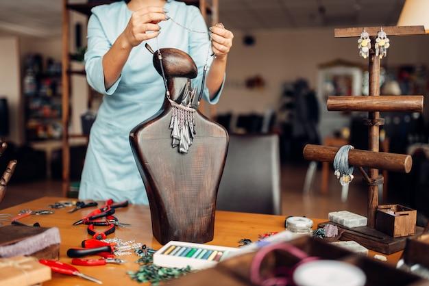 Persona di sesso femminile che prova sulla collana fatta a mano su un manichino di legno, cucito. artigiano femminile sul posto di lavoro in studio d'arte
