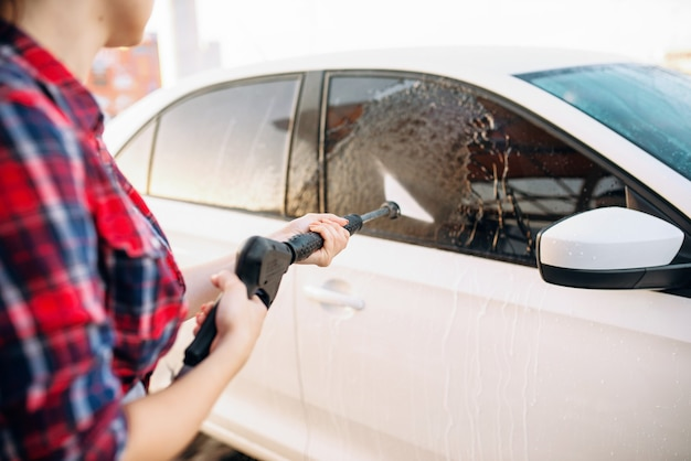 La persona di sesso femminile lava via la schiuma dal vetro dell'auto