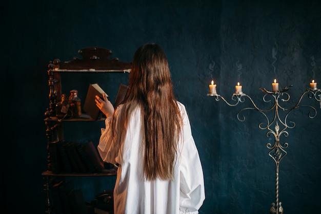 Persona di sesso femminile in camicia bianca mette il vecchio libro degli incantesimi sullo scaffale, vista posteriore, candele. magia oscura, occultismo ed esorcismo, stregoneria
