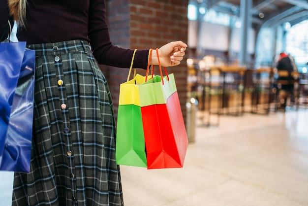 Persona di sesso femminile con le borse della spesa nel centro commerciale. shopaholic nel negozio di abbigliamento, stile di vita consumistico, moda, donna che acquista in negozio