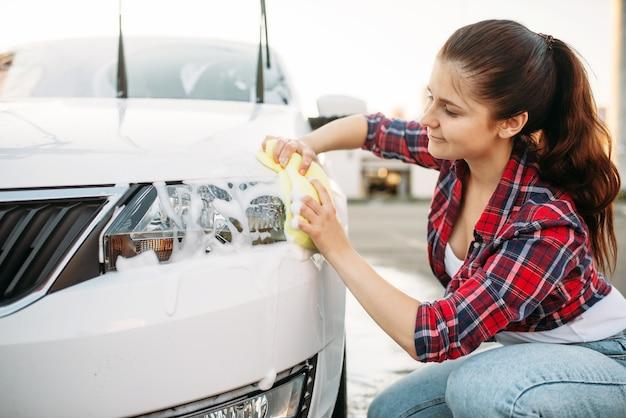 Persona di sesso femminile con la spugna pulisce il faro del veicolo