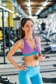 Personal trainer femminile con coda di cavallo e vestito con abiti sportivi che tengono appunti i risultati dell'allenamento mentre si trovava in una palestra e che guarda l'obbiettivo.