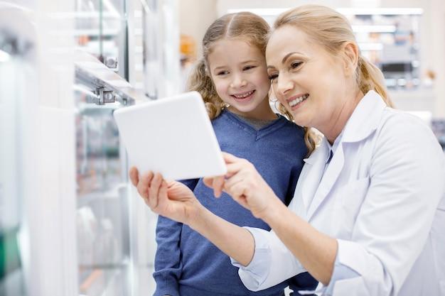 Farmacista femminile che aiuta una bambina in una farmacia