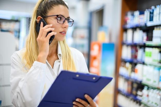 Farmacista donna che parla al telefono con un cliente nel suo negozio