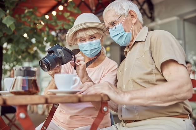 Fotografa con una maschera facciale che mostra le foto sulla sua fotocamera digitale a un uomo