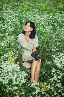 Fotografa femminile in possesso di una telecamera, seduta all'aperto sul campo di fiori che riposa con gli occhi chiusi, relax, donna che tiene in mano la fotocamera digitale. fotografia naturalistica di viaggio, spazio per il testo, vista dall'alto.