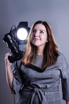 Una fotografa in uno studio con una fotocamera reflex e un'attrezzatura per l'illuminazione alza lo sguardo sognante. il concetto - nei sogni di diventare un grande fotografo