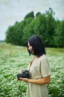 Il fotografo femminile prende la foto all'aperto sul paesaggio del campo di fiori che tiene una macchina fotografica, la donna tiene la macchina fotografica digitale nelle sue mani. fotografia naturalistica di viaggio, spazio per il testo, vista dall'alto.