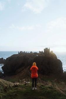Fotografo femminile che prende foto del castello di dunnottar, scozia
