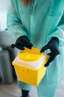 Un fisioterapista femminile che lancia un ago di agopuntura in un contenitore giallo di rifiuti medici
