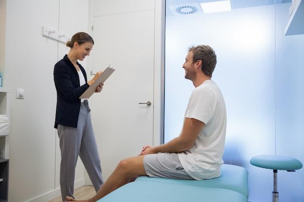Il fisioterapista femminile consulta il giovane paziente