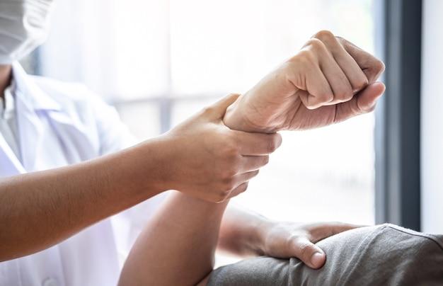 Fisioterapista femminile che lavora esaminando il trattamento del braccio ferito di un paziente maschio atleta, stretching ed esercizio fisico, facendo il dolore della terapia riabilitativa in clinica.