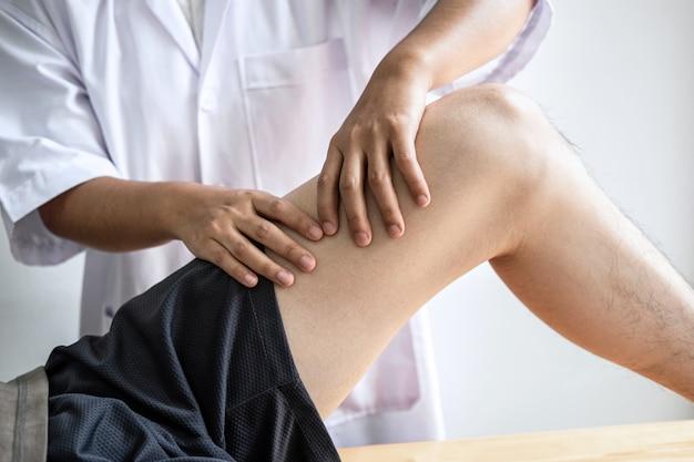 Fisioterapista femmina lavorando esaminando il trattamento della gamba ferita del paziente maschio, facendo esercizi di riabilitazione terapia dolore suo in clinica