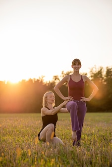 Istruttore di pilates femminile che apporta correzioni al suo tirocinante mentre si esercita all'esterno in un bellissimo prato retroilluminato dal sole della sera.