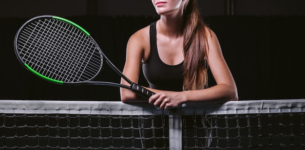 Giocatrice che tiene una racchetta da tennis dalla rete