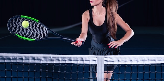 Giocatrice che tiene una racchetta da tennis con la palla