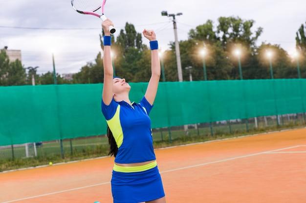 La giocatrice è felice e ha alzato le mani per la vittoria nella partita di tennis sul campo da tennis in terra battuta in estate o in primavera
