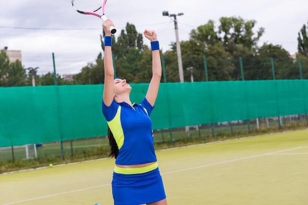 La giocatrice è felice e ha alzato le mani a causa della vittoria nella partita di tennis sul campo da tennis in erba verde in estate o in primavera