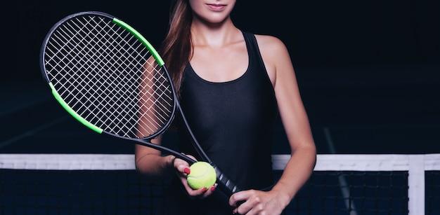 Giocatrice con racchetta da tennis e palla seduta vicino alla rete