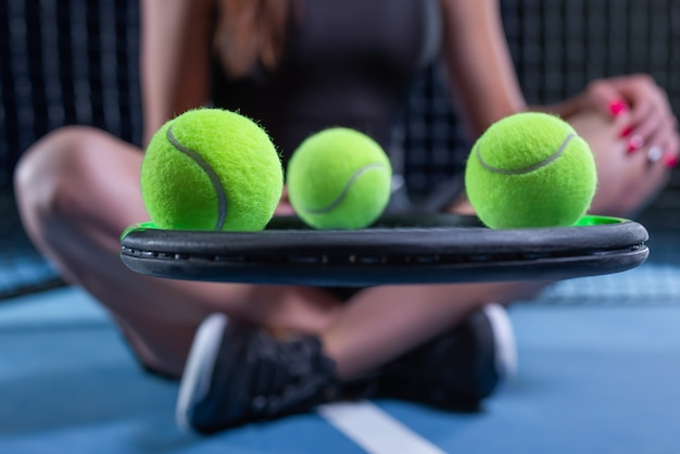 Giocatrice con racchetta da tennis e palline seduta vicino alla rete