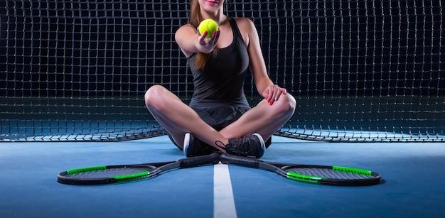 Giocatrice con racchette da tennis e palla seduta vicino alla rete