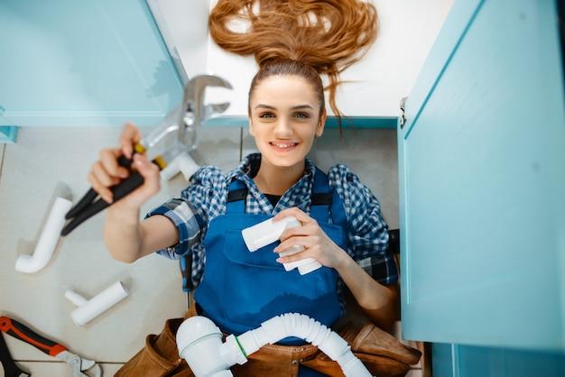 Idraulico femmina con chiave e tubo sdraiato sul pavimento in cucina, vista dall'alto. tuttofare con lavello per la riparazione della borsa degli attrezzi, servizio di attrezzature sanitarie a casa