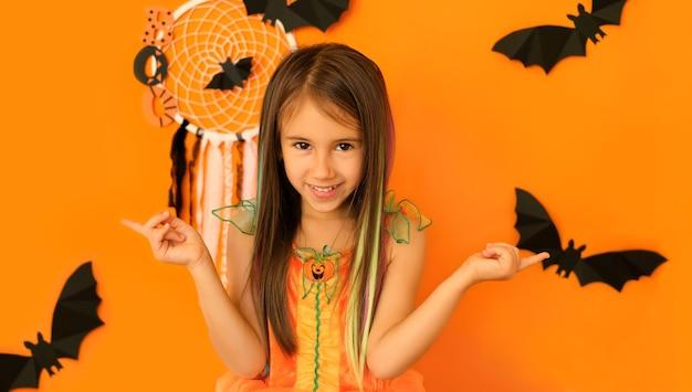 La femmina che punta il dito su uno sfondo arancione da studio con decorazioni di halloween