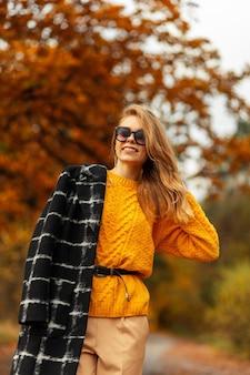 Il ritratto femminile di una ragazza felice con i vestiti alla moda e un maglione lavorato a maglia giallo cammina in un parco di autunno in natura
