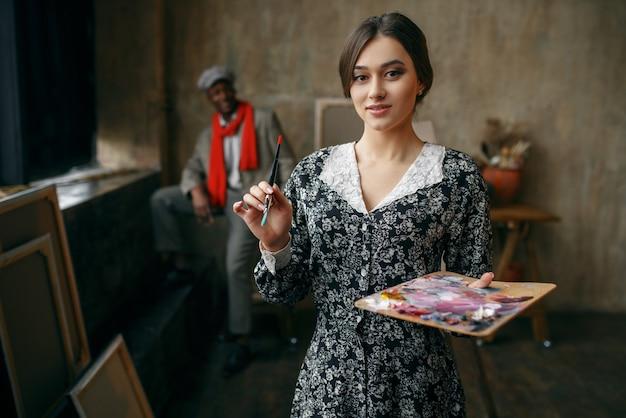 Il ritrattista femminile tiene la tavolozza e il pennello, modello maschile in studio d'arte. artista maschio in piedi al suo posto di lavoro, maestro creativo in officina