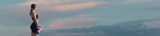 Posa femminile in abiti sportivi sullo sfondo del cielo. la parte centrale del corpo.