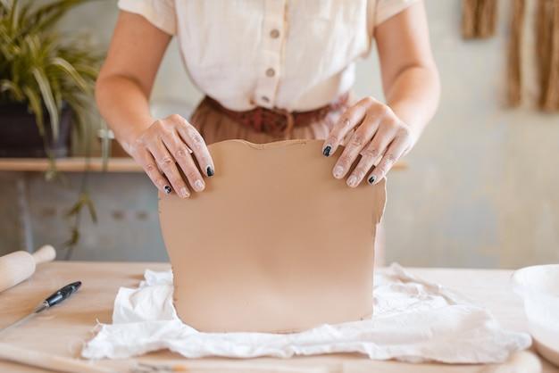 Potter femmina tiene frittella di argilla, laboratorio di ceramica