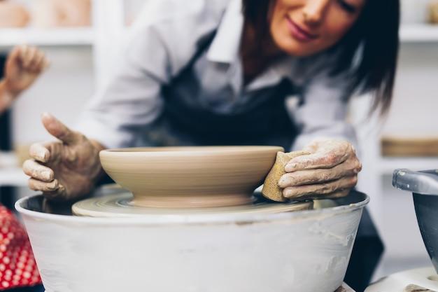 Potter femmina che fa ceramica di argilla su una ruota di rotazione.