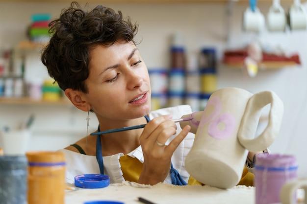 Potter femmina pittura su brocca di argilla in officina che lavora in ceramica studio hobby piccola impresa