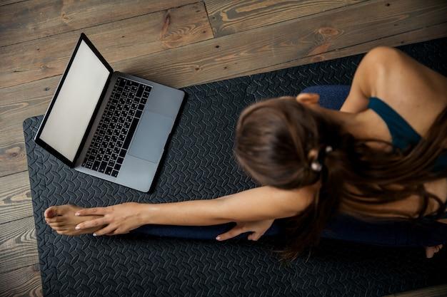 Donna che pratica yoga o pilates al chiuso sul materassino, fa esercizi e stretching, guarda video lezione online. vista dall'alto