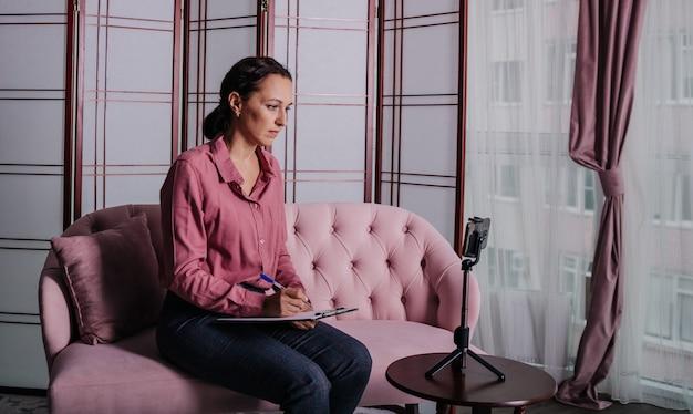 Una psicologa in abiti da lavoro si siede su un divano rosa e conduce una consultazione online usando il suo telefono