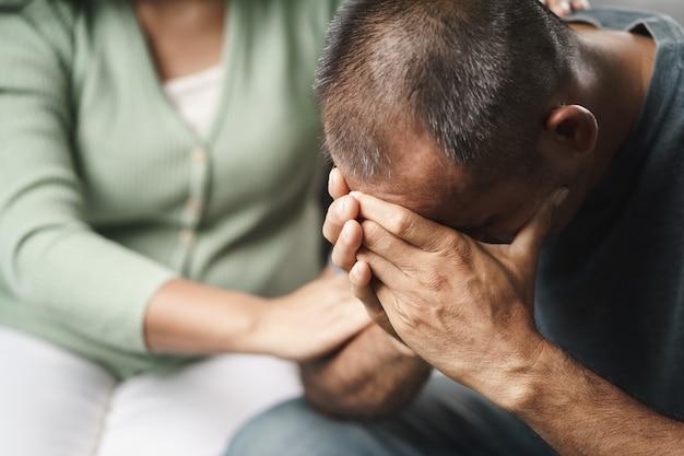 Psicologa, amica o famiglia seduta e mettere le mani sulla spalla per rallegrare l'uomo depresso mentale, la psicologa fornisce aiuto mentale al paziente. ptsd concetto di salute mentale.