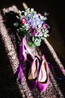 Scarpe da sposa in velluto viola femminile su sfondo beige e bouquet di fiori. accessori da sposa. vista dall'alto.