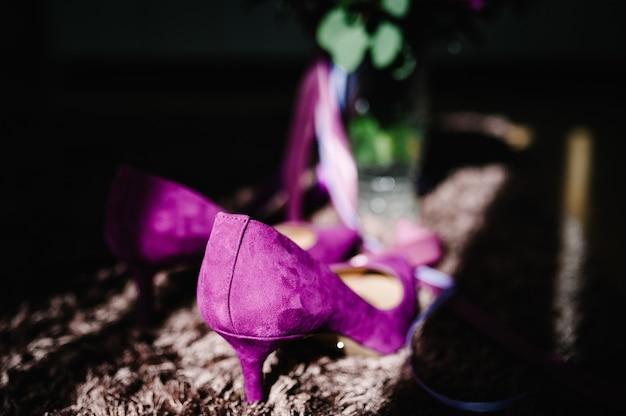 Scarpe da sposa in velluto viola femminile su fondo beige. accessori da sposa. vista posteriore.