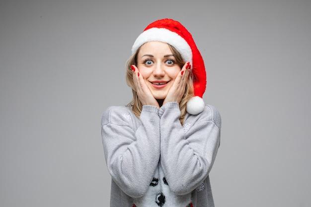 Femmina che si mette le mani sulle guance incredula dopo aver ricevuto una sorpresa dei suoi sogni. copia spazio. anno nuovo concetto