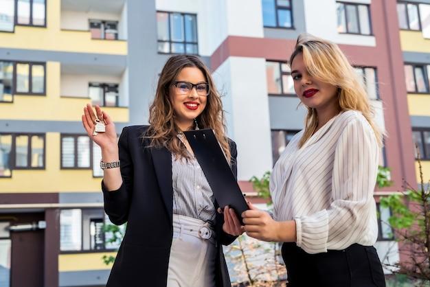 Agente immobiliare femminile con chiave per appunti e cliente giovane donna vicino a casa in vendita all'aperto